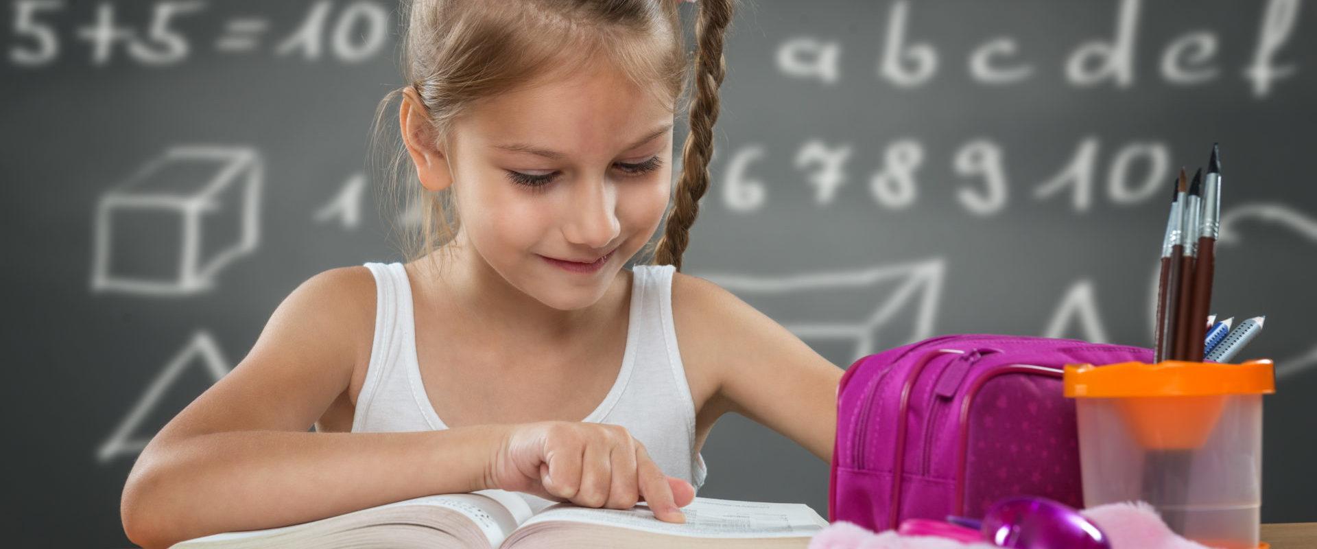 Little girl reading in school, written job behind the plate